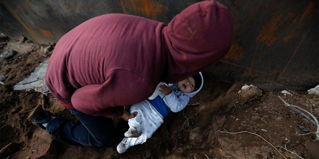 Honduran migrant Joel Mendez, 22, passing his eight-month-old son Daniel through a hole under the U.S. border wall to his partner, Yesenia Martinez, 24, who had already crossed in Tijuana, Mexico, on Friday. (AP Photo/Rebecca Blackwell)