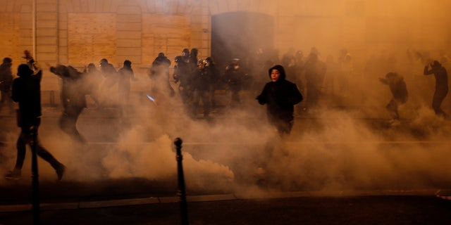 Demonstrators run away to avoid tear gas during clashes Saturday, Dec. 8, 2018 in Paris.