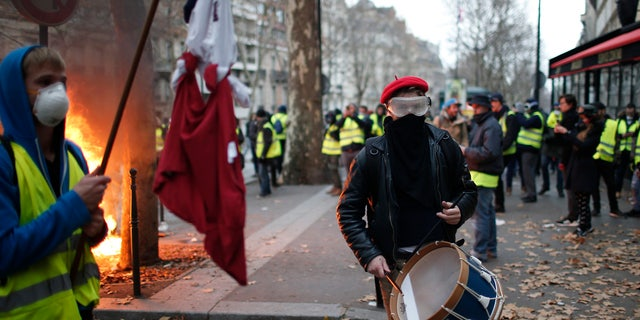 Crowds of yellow-vested protesters angry at President Emmanuel Macron and France's high taxes tried to converge on the presidential palace Saturday, some scuffling with police firing tear gas, amid exceptional security measures aimed at preventing a repeat of last week's rioting