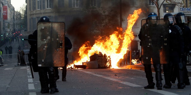 Riot police officer stand in front a burning trash bin during clashes, Saturday, Dec. 8, 2018 in Marseille, southern France.