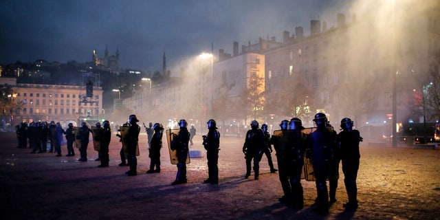 Police officers face demonstrators in Lyon, central France, Saturday, Dec. 8, 2018. The grassroots movement began as resistance against a rise in taxes for diesel and gasoline, but quickly expanded to encompass frustration at stagnant incomes and the growing cost of living. (AP Photo/Laurent Cipriani)