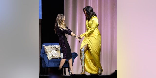"NEW YORK, NEW YORK - DECEMBER 19: Former first lady Michelle Obama (R) discusses her book ""Becoming"" with Sarah Jessica Parker at Barclays Center on December 19, 2018 in New York City. (Photo by Dia Dipasupil/Getty Images)"