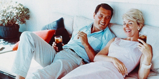 Rock Hudson (1925-1985) and Doris Day laughing and holding drinks, circa 1960. — Getty