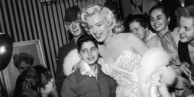 "Marilyn Monroe is all smiles as she poses with fans in front of the Wilshire Beauty Shop at the premiere of director Jean Negulesco's film ""How to Marry a Millionaire"" in 1953."