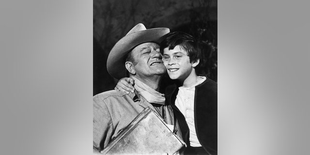 Ethan Wayne, 8, gets a hug from dad, John Wayne, after filming a shootout scene with outlaws in 'The Million Dollar Kidnapping.'
