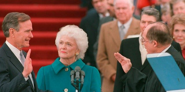 In this Jan. 20, 1989 photo, President George H.W. Bush raises his right hand as he is sworn into office as the 41st president of the United States by Chief Justice William Rehnquist as first lady Barbara Bush holds the Bible for her husband. (AP Photo/Bob Daugherty, File)