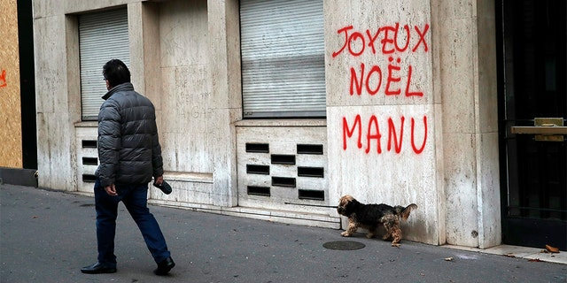 A man walking his dog past a tag reading: Happy Christmas Manu, referring to French President Emmanuel Macron, in Paris, Sunday. (AP Photo/Christophe Ena)