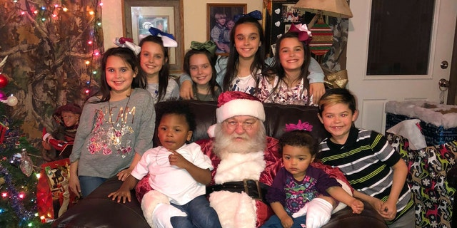 All but one of the Hawthorn's adopted kids pose with Santa as they will all be celebrating Christmas as one family this year.