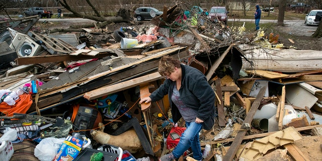 Joyce Morrissey sorting through the debris of her nephew Stephen Tirpak's house in Taylorville, Ill., Sunday. The National Weather Service said multiple tornadoes touched down in central Illinois, damaging dozens of structures and injuring multiple people. (Ted Schurter/The State Journal-Register via AP)