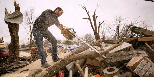 Steven Tirpak using a chainsaw to remove tree branches that fell onto his two-story home in Taylorville, Ill., Sunday. (Ted Schurter/The State Journal-Register via AP)
