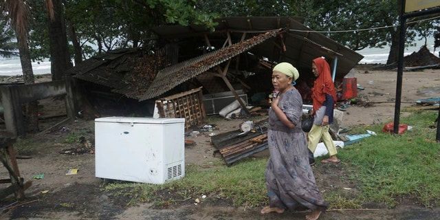 Residents walk past a house damaged by a tsunami, in Carita, Indonesia, Sunday, Dec. 23, 2018. (Associated Press)
