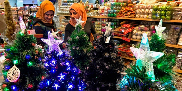 Iraqis shop for Christmas decorations in Baghdad, Iraq, Monday, Dec. 24, 2018. (AP Photo/Ali Abdul Hassan)
