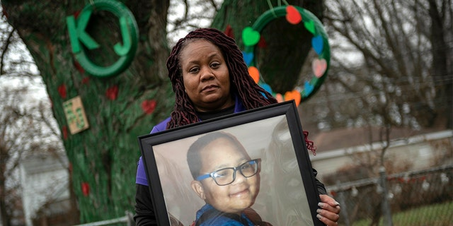LaSondra Singleton holding a photo of her son Kenneth Gross Jr. while standing in front of a tree that was decorated in the child's honor at her Warren, Mich., home. Kenneth died at age 12 waiting for a donor heart that failed due to complications from cancer. (David Guralnick/Detroit News via AP)