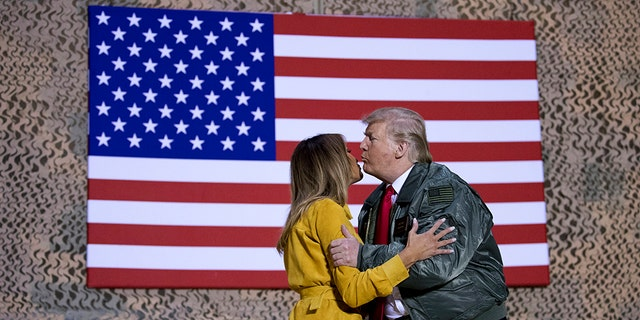 President Trump and the first lady during a hangar rally at Al Asad Air Base, Iraq, Wednesday. (AP Photo/Andrew Harnik)