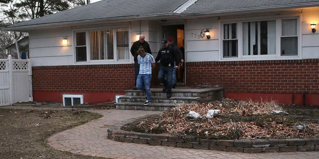 ICE agents detain a suspected MS-13 gang member and Honduran immigrant at his home in Brentwood, N.Y., in March.