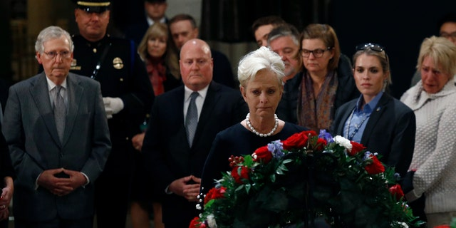 Cindy McCain, center, widow of the late Sen. John McCain, R-Ariz., views the flag-draped casket of former President George H.W. Bush as he lies in state in the Capitol Rotunda on Tuesday. At back left is Senate Majority Leader Mitch McConnell, R-Ky. (AP Photo/Patrick Semansky)