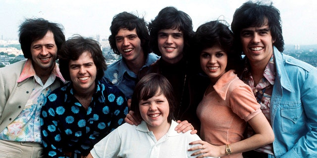 A group portrait of The Osmonds in London in 1975. Da sinistra a destra, Wayne Osmond, Merrill Osmond, Jay Osmond, Jimmy Osmond, Donny Osmond, Marie Osmond, Alan Osmond.