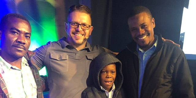 """Pastor Paul Boutan of Calvary Chapel Brighton in Colorado poses with """"Little John,"""" his father, Jean Olivier, and their translator, Luccone Lucce Sunday following a successful surgery in Connecticut."""