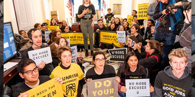 Protesters seen holding placards during the Sunrise Movement protest to advocate that Democrats support the Green New Deal, at the US Capitol.