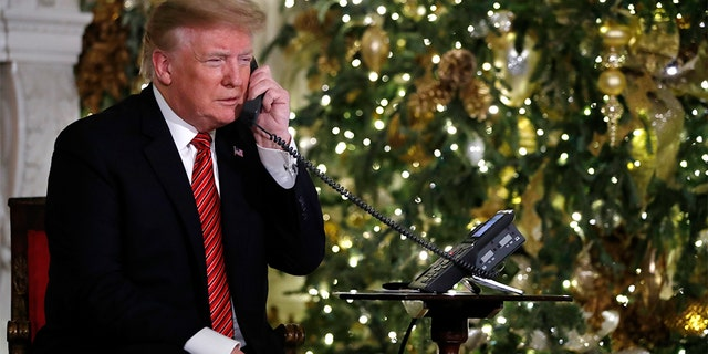 President Donald Trump speaks on the phone sharing updates to track Santa's movements from the North American Aerospace Defense Command (NORAD) Santa Tracker on Christmas Eve, Monday, Dec. 24, 2018. (AP Photo/Jacquelyn Martin)