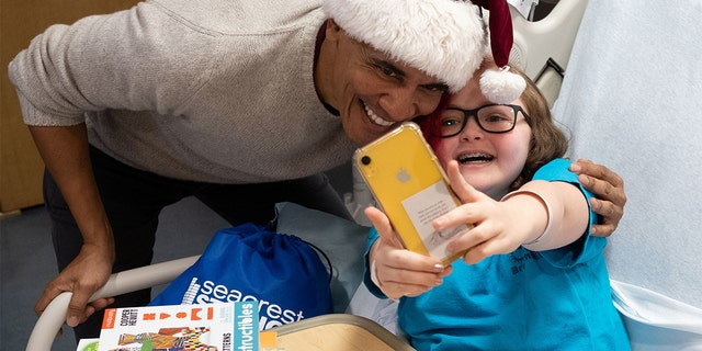 Obama bends down for a selfie with a young patient.