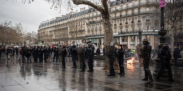 The student protesters marched through Paris to the Republic Square, where they recreated the arrest scene while being surrounded by police officers wearing riot gear.