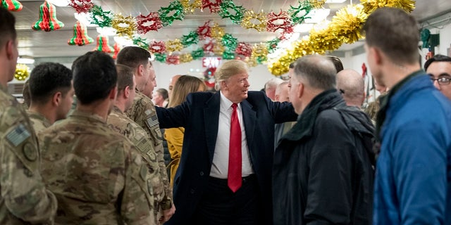 President Donald Trump visits with members of the military at a dining hall at Al Asad Air Base, Iraq, Wednesday, Dec. 26, 2018. (AP Photo/Andrew Harnik)