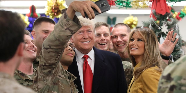 The first couple welcomed the military personnel during the festival an unannounced visit to the Al Asad Air Base. (REUTERS / Jonathan Ernst)