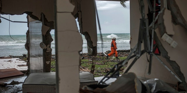 A rescuer is seen through a damaged house as he takes part in a search operation of tsunami victims in Carita, Indonesia, Sunday. (AP Photo/Fauzy Chaniago)
