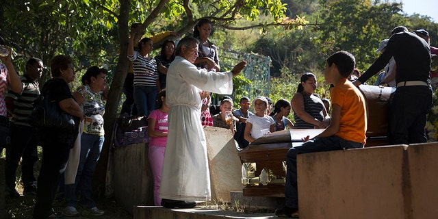 Atilio Gonzalez (C), a priest of the Southern Cemetery for the last 24 years, prays during a burial ceremony at the Southern Cemetery in Caracas January 28, 2014. Since then, proper burials have become too expensive for the vast majority of the population.