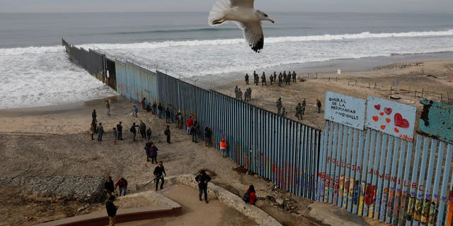 People look on from the Mexican side, left, as U.S. Border Patrol agents on the other side of the U.S. border wall in San Diego prepare for the arrival of hundreds of pro-migration protestors, seen from Tijuana, Mexico, Monday, Dec. 10, 2018. (AP Photo/Rebecca Blackwell)