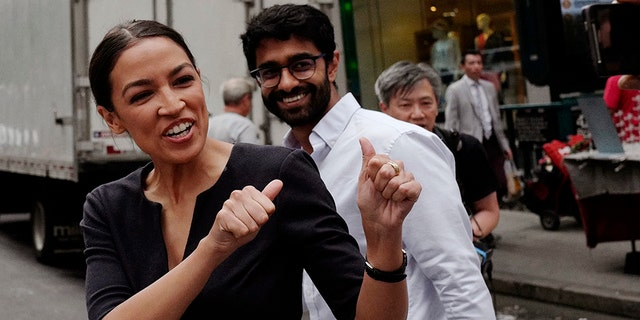 FILE - In this Wednesday June 27, 2018, file photo, Alexandria Ocasio-Cortez, left, the winner of New York's Democratic Congressional primary, greets supporters following her victory, along with Saikat Chakrabarti, founder of Justice Democrats and senior adviser for her campaign. (AP Photo/Mark Lennihan, File)