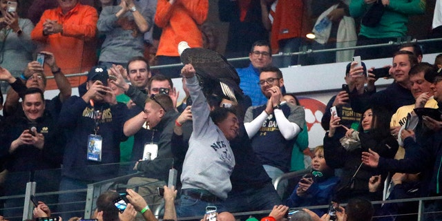 """Fans cheer as """"Clark,"""" an American bald eagle, lands on the arm of a fan in the upper deck after the playing of the national anthem before the first half of the NCAA Cotton Bowl semi-final playoff football game between Clemson and Notre Dame on Saturday, Dec. 29, 2018, in Arlington, Texas."""