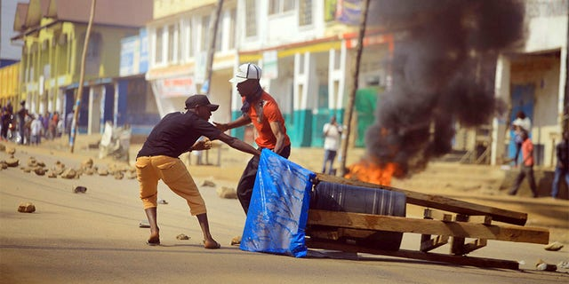 Protesters set up a barricade in the Eastern Congolese city of Beni on Thursday. Police in eastern Congo have fired live ammunition and tear gas to disperse dozens of people protesting a presidential election delay that means more than 1 million votes will not count.