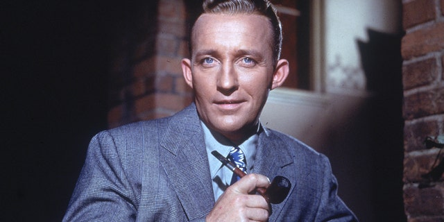 American actor and singer Bing Crosby poses for a portrait holding a pipe in his hand in 1948.