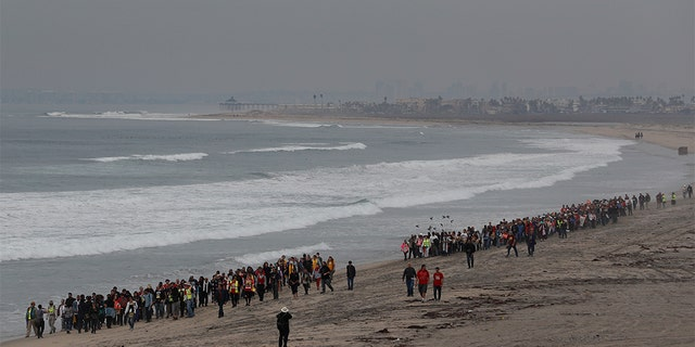Members of various faith groups walking on the beach toward the U.S. border with Mexico. (AP Photo/Rebecca Blackwell)