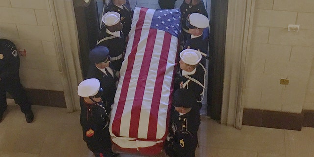 A military honor guard marches the casket of former President George H.W. Bush into the U.S. Capitol on Monday.