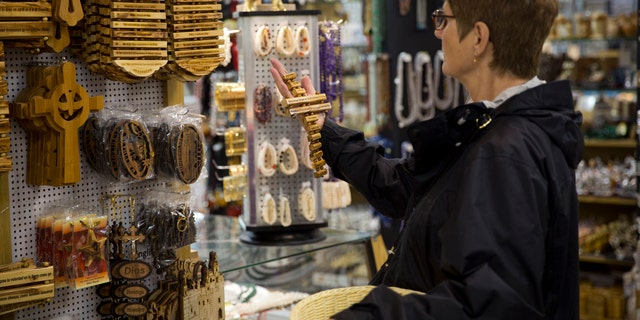 A woman visits a shop near the Church of the Nativity, built atop the site where Christians believe Jesus Christ was born, in the West Bank City of Bethlehem. (AP Photo/Majdi Mohammed)