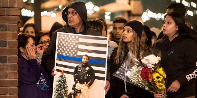 In this Friday, Dec. 28, 2018, photo, family members of police Cpl. Ronil Singh including Birend Singh, holding picture at left, attend a candlelight vigil for the slain officer in downtown Newman, Calif.