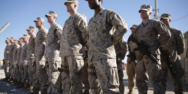 FILE - In this Jan. 15, 2018 file photo, U.S. Marines stand guard during the change of command ceremony at Task Force Southwest military field in Shorab military camp of Helmand province, Afghanistan. The Pentagon is developing plans to withdraw up to half of the 14,000 American troops serving in Afghanistan, U.S. officials said Thursday, Dec. 20, 2018, marking a sharp change in the Trump administration's policy aimed at forcing the Taliban to the peace table after more than 17 years of war. (AP Photo/Massoud Hossaini, File)