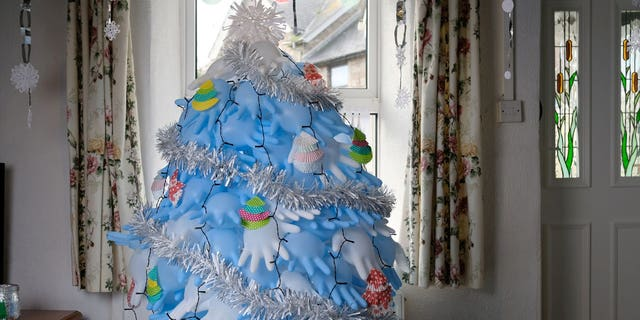 Along with surgical gloves, the tree is decorated with cupcake liners and candy wrappers.