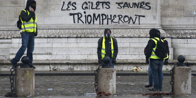 "Demonstrators stand by the words ""yellow jackets will triumph"" written in black letters at the base of the Arc de Triomphe during a demonstration Saturday, Dec.1, 2018 in Paris."