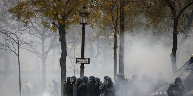 French riot police officers take position amid tear gas during a demonstration Saturday, Dec. 1, 2018 in Paris. French authorities have deployed thousands of police on Paris' Champs-Elysees avenue to try to contain protests by people angry over rising taxes and Emmanuel Macron's presidency.