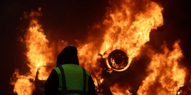A demonstrator watches a burning car near the Champs-Elysees avenue during a demonstration Saturday in Paris.
