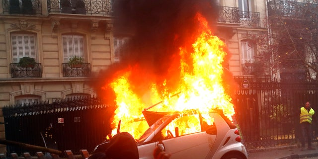 A hooded malcontent throws an object as a automobile buns during a proof Saturday, Dec.1, 2018 in Paris. Protesters indignant about rising taxes clashed with French military for a third true weekend and over 100 were arrested after pockets of demonstrators built barricades in a center of streets in executive Paris, illuminated fires and threw rocks during officers Saturday. (AP Photo/Thibault Camus)