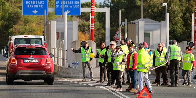 Demonstrators wearing yellow vests protest at the toll gates of a motorway, in Biarritz, southwestern France, Monday, Dec. 10, 2018.
