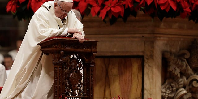 Pope Francis kneels on the altar as he celebrates the Christmas Eve Mass in St. Peter's Basilica at the Vatican.