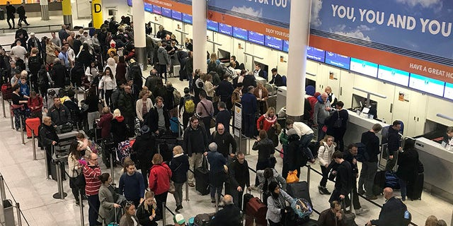 Passengers wait to check in at Gatwick Airport on Friday.