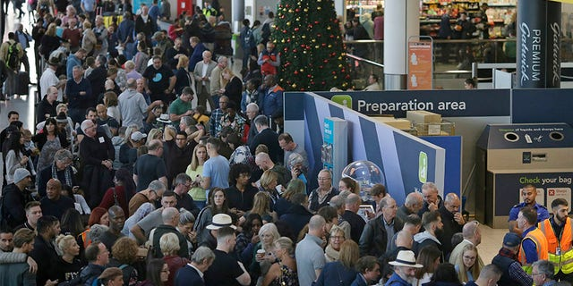 People wait near the departures gate at Gatwick airport, near London, as the airport remains closed with incoming flights delayed or diverted to other airports, after drones were spotted over the airfield last night and this morning.