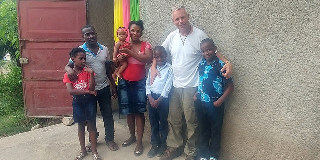 "Barclay Stuart with John ""Little John"" Olivier's family in Haiti before the nine-year-old Haitian received the life-saving surgery."